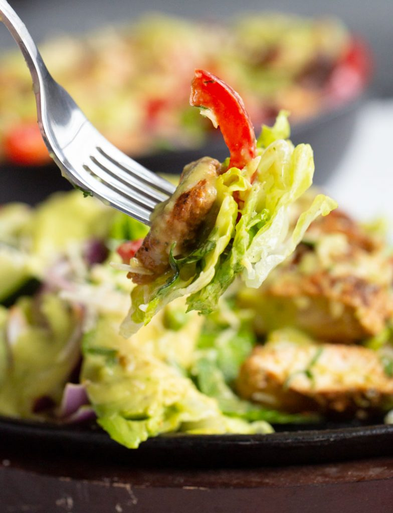a fork holding a bite of fajita chicken salad