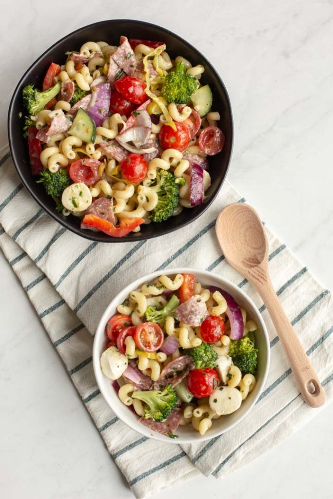 Italian pasta salad in a bowl on a table with a wooden spoon