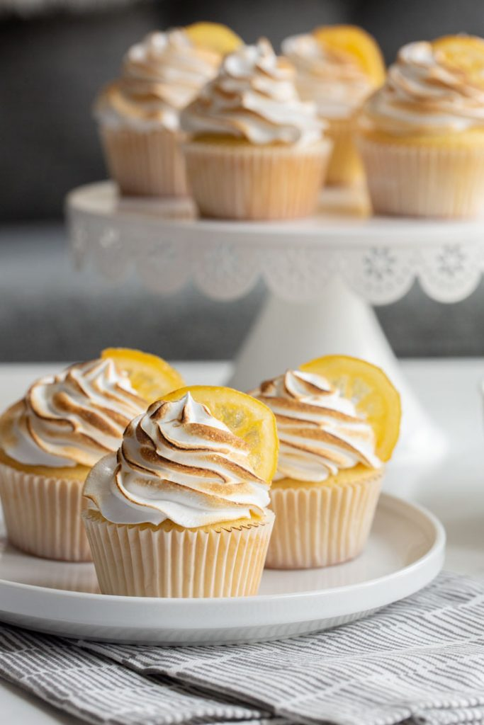 lemon meringue cupcakes topped with candied lemons on a plate