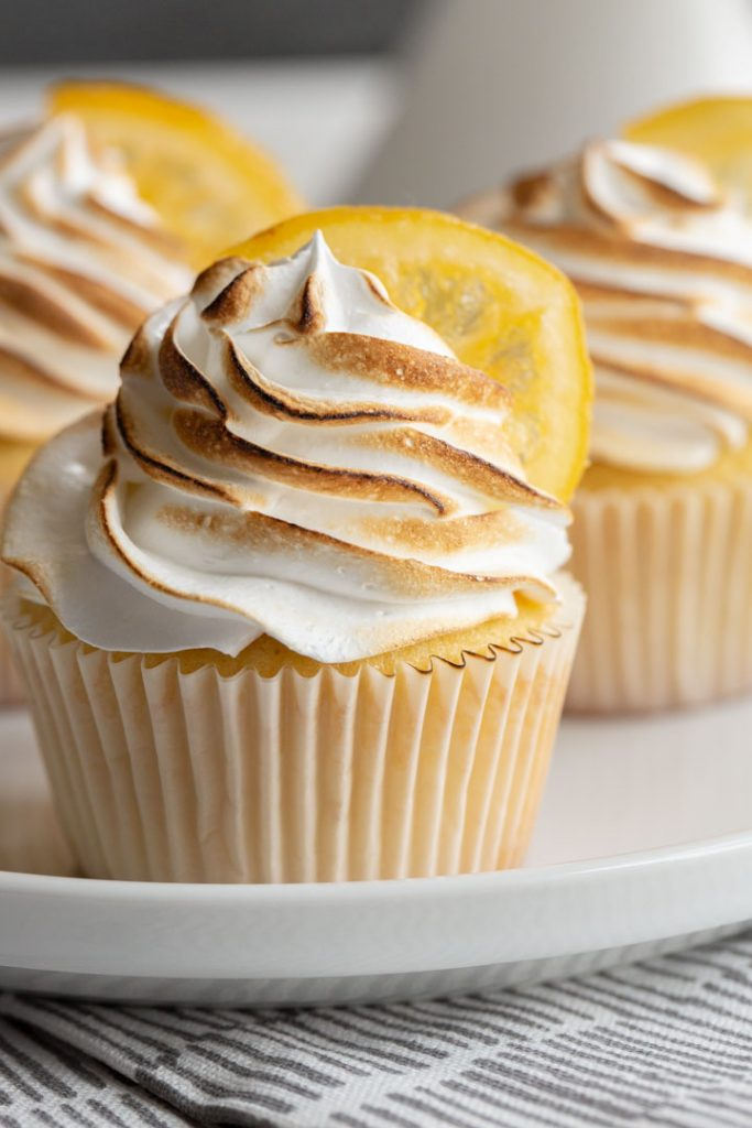 lemon meringue cupcakes with a marshmallow frosting that has been slightly charred with a candied lemon on top