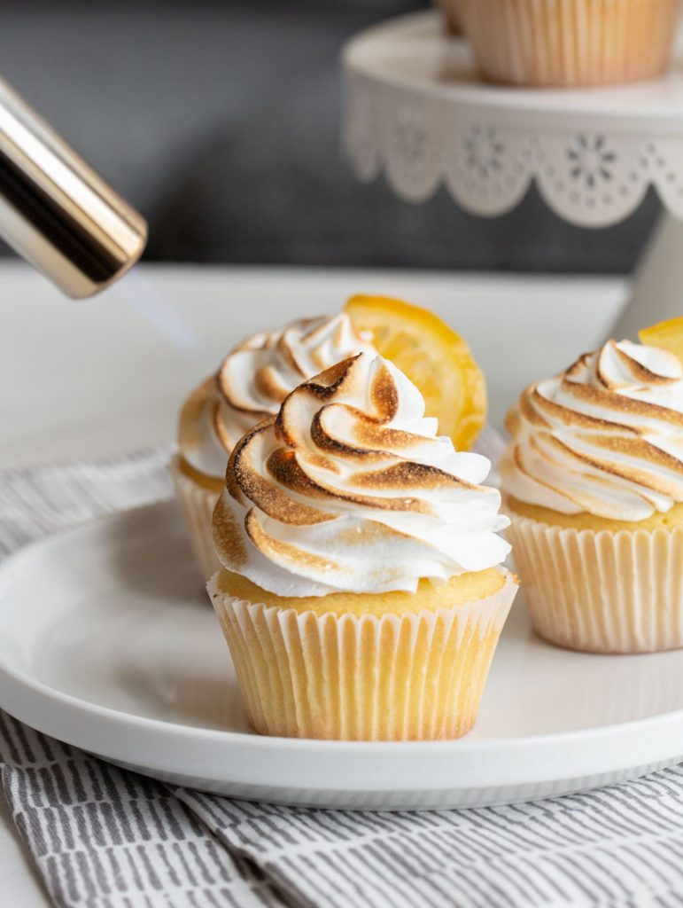 lemon meringue cupcakes being charred by a culinary torch