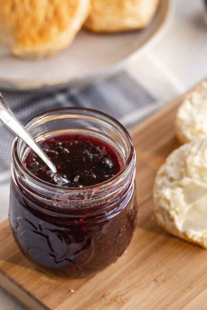 mixed berry jam in a jar with a spoon