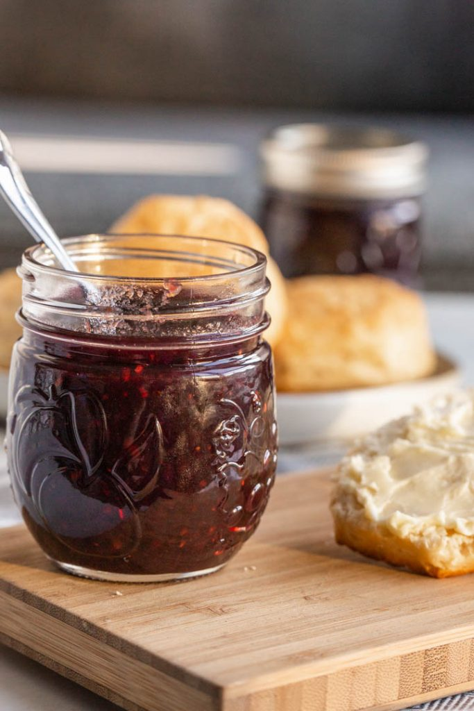 mixed berry jam made from summer fruits in a jar with a spoon
