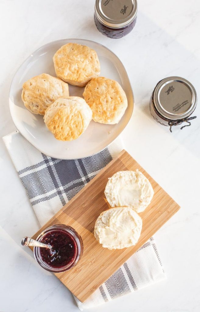 a plate of biscuits with a jar of mixed berry jam
