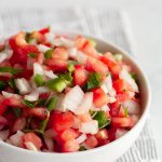 pico de gallo in a white bowl on a gray towel