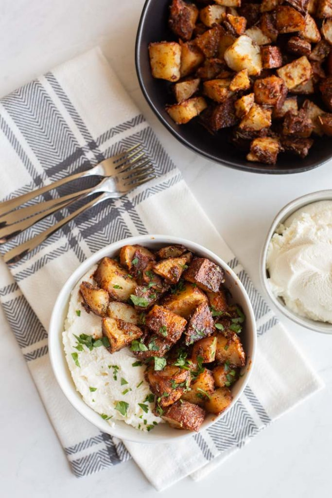 spicy roasted potatoes in a bowl with ricotta cheese and honey