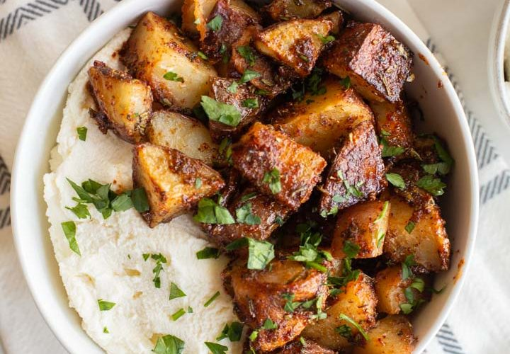 sweet and spicy roasted potatoes in a bowl with ricotta cheese and honey