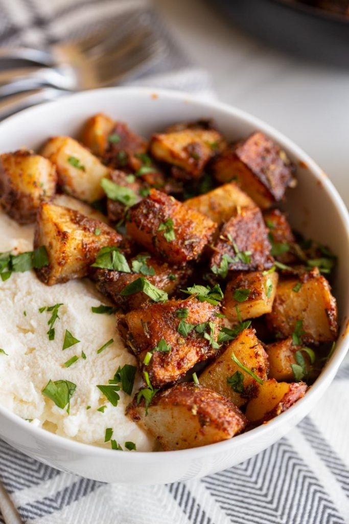 spicy roasted potatoes in a bowl with honey and ricotta