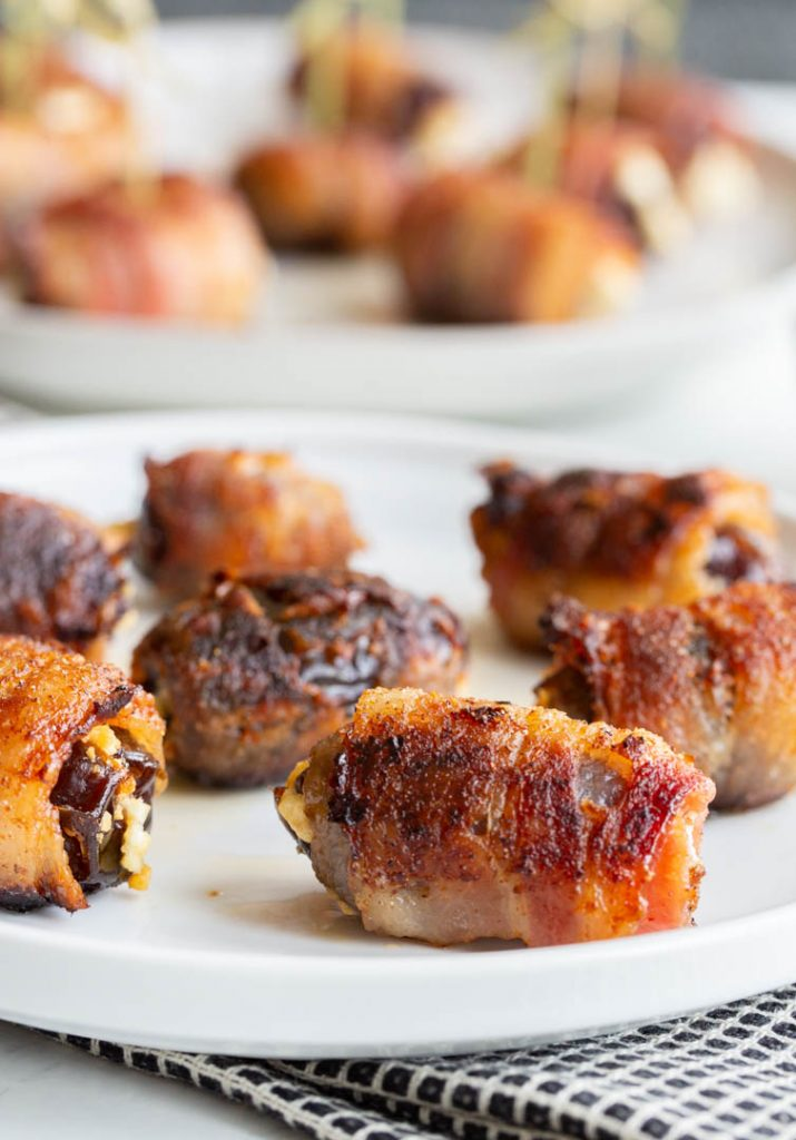 bacon wrapped dates on a plate with a towel