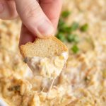 hot crab dip being scooped up with a crisp
