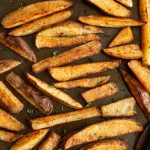 Seasoned potato wedges on a sheet pan
