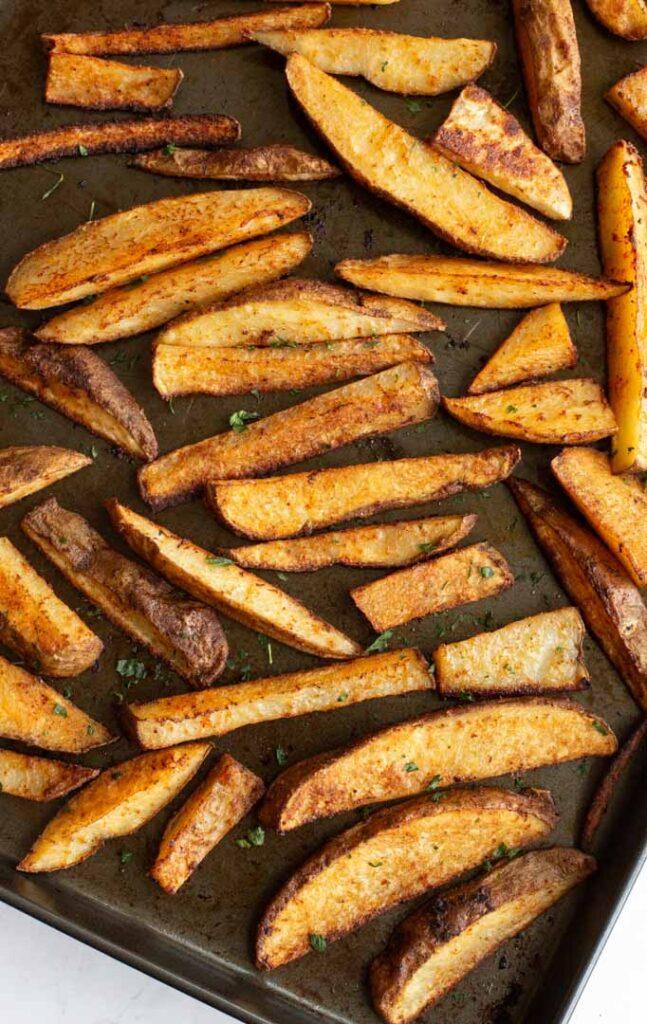 Seasoned potato wedges on a sheet pan