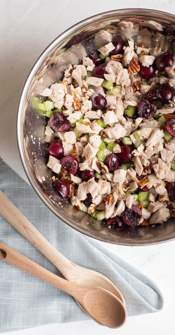 cherry chicken salad mixture with chicken, celery, cherries and pecans in a bowl