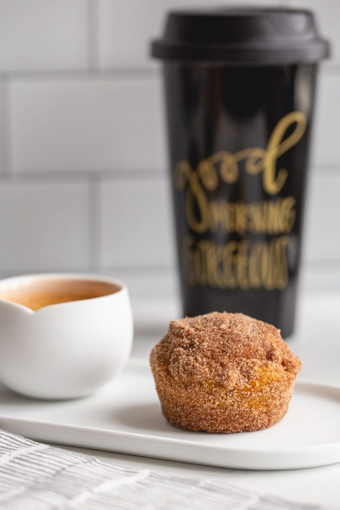 one pumpkin muffin on a plate with a shot of espresso