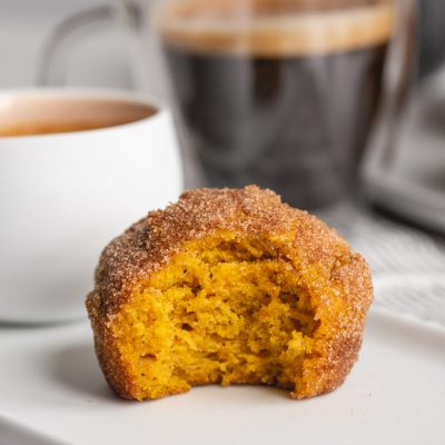 a pumpkin muffin rolled in cinnamon sugar on a plate with a cup of coffee
