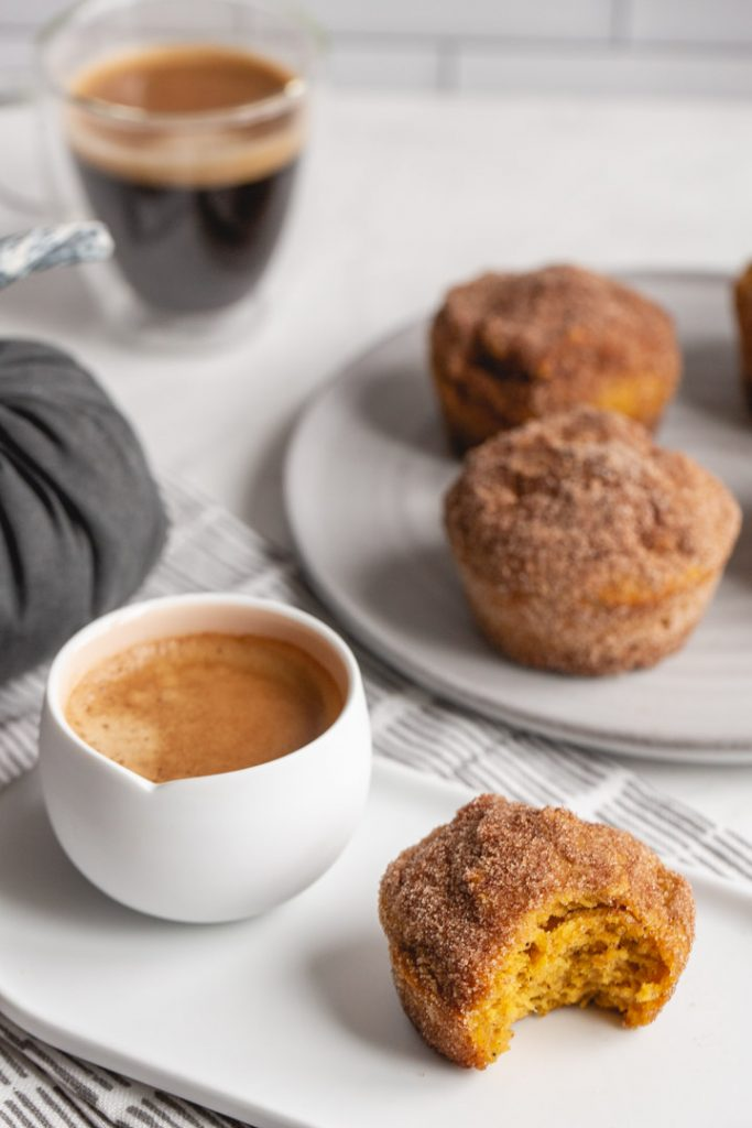 several pumpkin muffins on a plate with coffee and cinnamon sugar