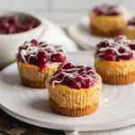 mini pumpkin cheesecakes on a plate topped with cranberry compote and white chocolate