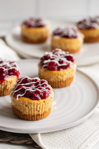 mini pumpkin cheesecakes topped with a cranberry compote and white chocolate
