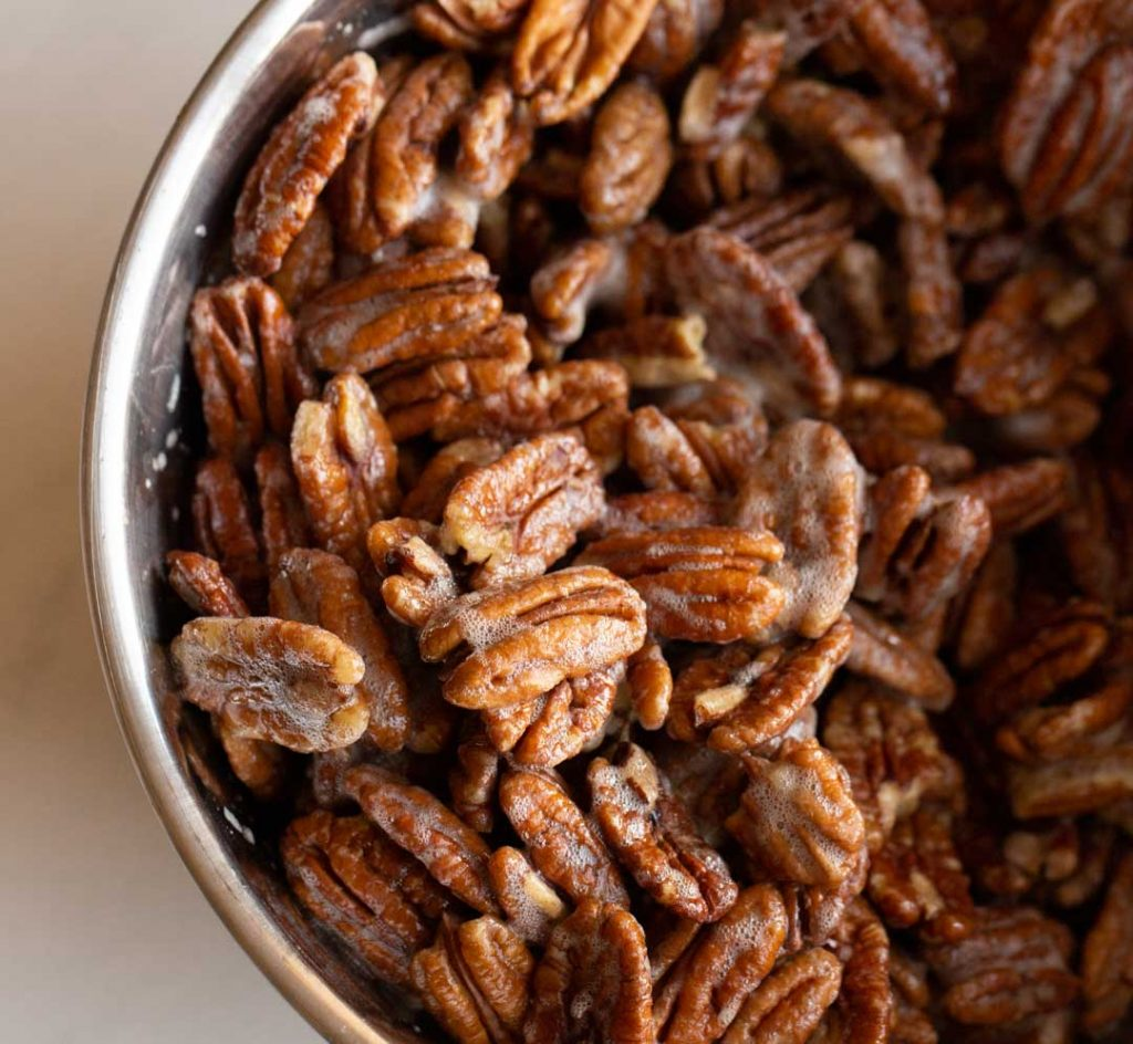 pecans in a bowl tossed with egg whites and vanilla