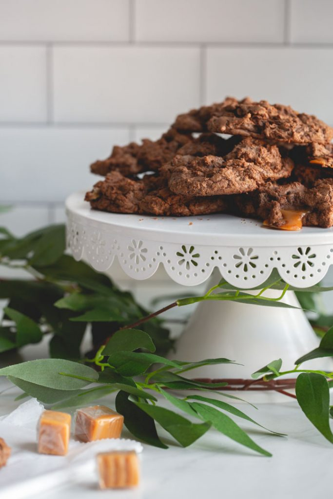chocolate cookies with caramel and pecans on a stand