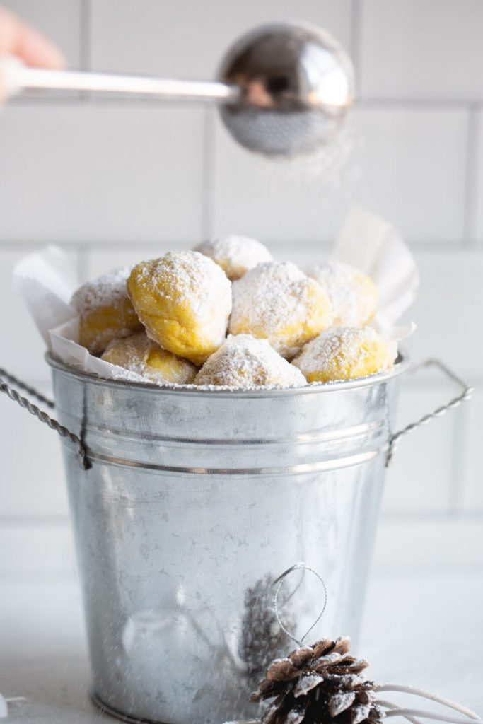 lemon snowball cookies being dusted with powdered sugar