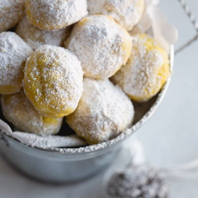 lemon snowball cookies in a tin with parchment