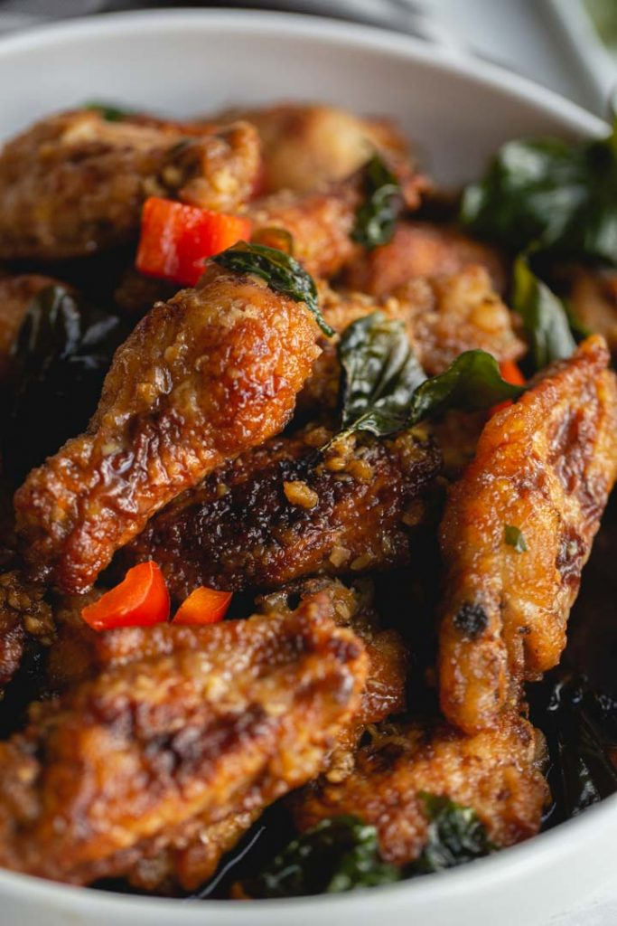 close up of fried chicken wings tossed in garlic sauce