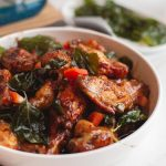crispy garlic chicken wings in a bowl garnished with fried basil and red pepper