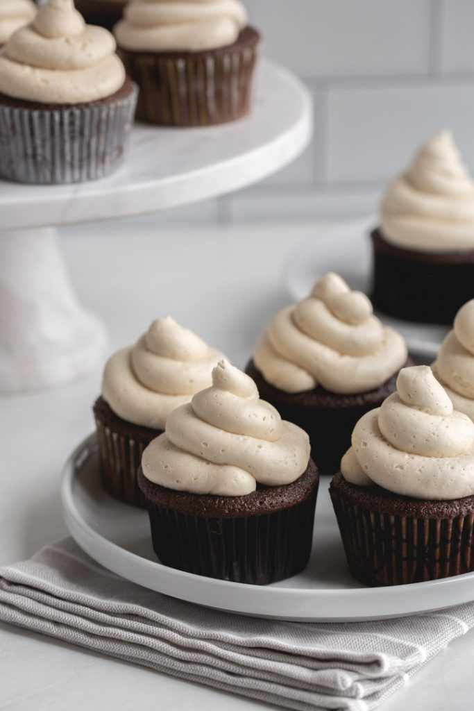 chocolate kahlua cupcakes topped with kahlua frosting on a plate and cake stand