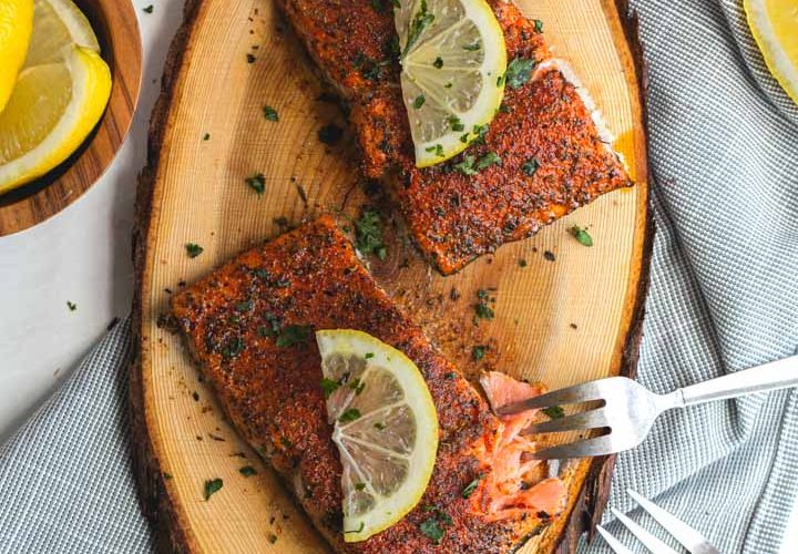 two filets of blackened salmon on a cedar plank with lemon slices