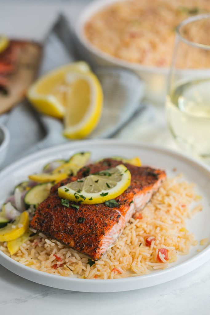 blackened salmon served on a bed of rice on a white plate