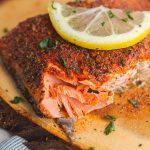 blackened salmon on a cedar plank with a lemon slice on top