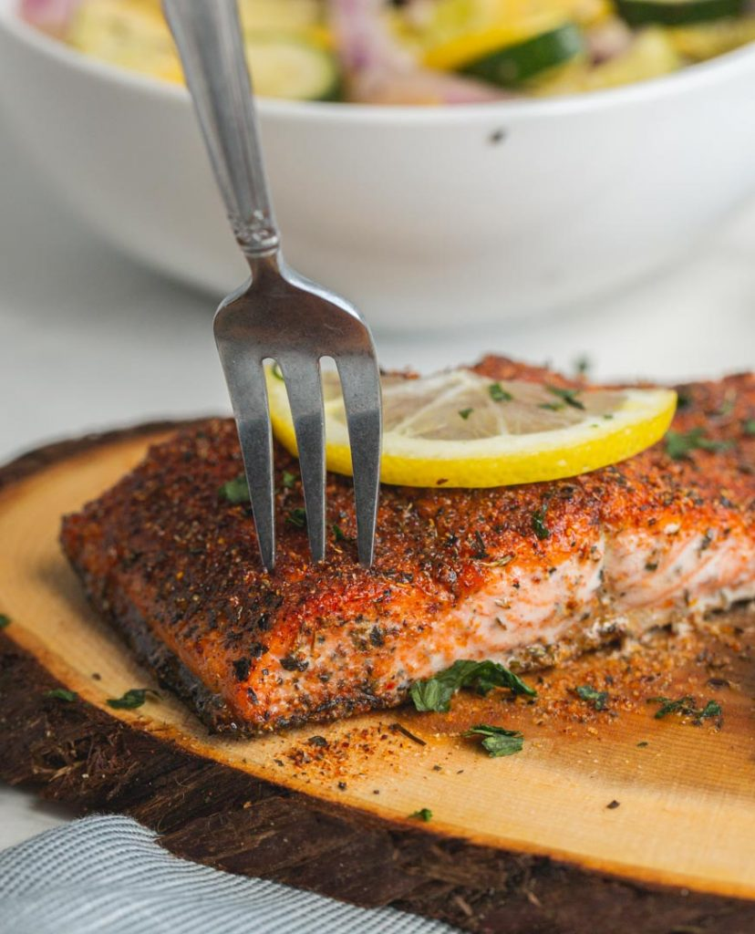 a fork taking out a piece of cedar plank salmon with a lemon on top