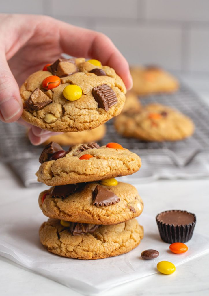hand placing peanut butter cup cookie on top of large stack of cookies