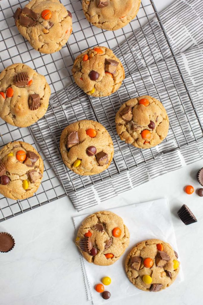 several peanut butter cookies laying on a cooling rack with peanut butter candies