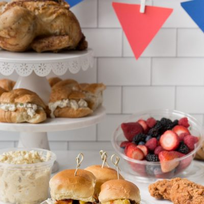 bbq sliders, fresh fruit, cookies, sandwiches and chicken laid out in a party spread
