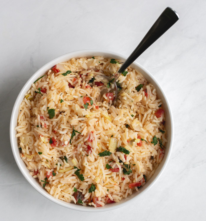 basmati rice pilaf in a bowl with a spoon sticking out