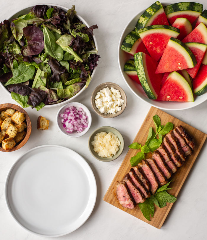 empty plate surrounded by ingredients for a steak and watermelon salad