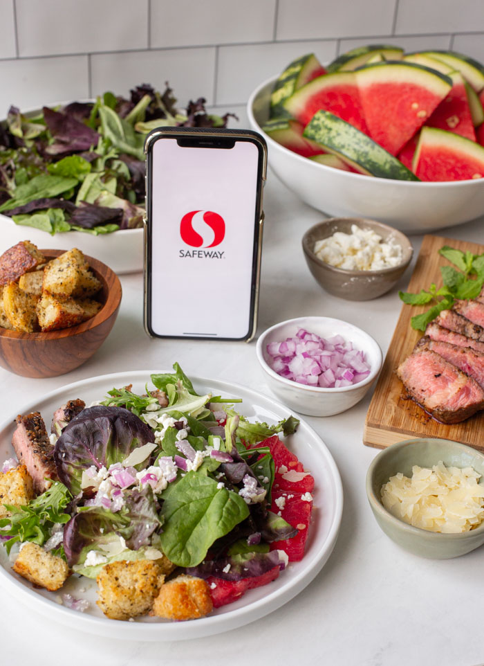 steak and watermelon salad on a plate with a phone displaying the safeway app