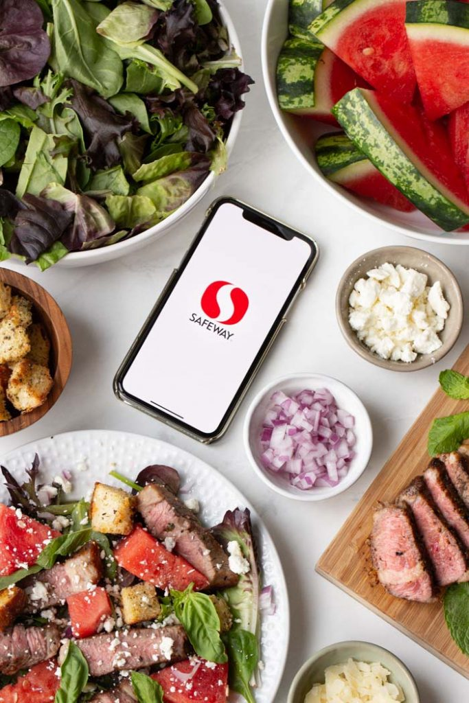 steak and watermelon salad with feta on a plate with safeway app displayed on phone