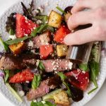 plate with lettuce, steak, watermelon, feta and red onion dressed with balsamic vinaigrette