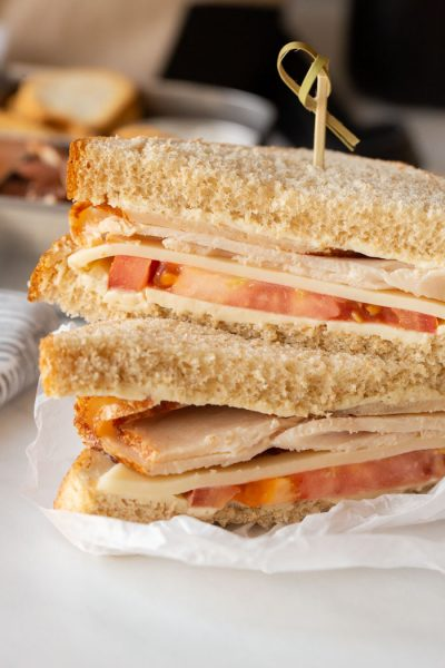 turkey and swiss cheese sandwich stacked on a paper and fastened with a toothpick