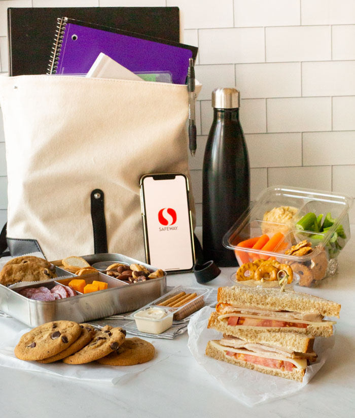 backpack with books, water bottle, phone and packed school lunch with turkey and swiss sandwich