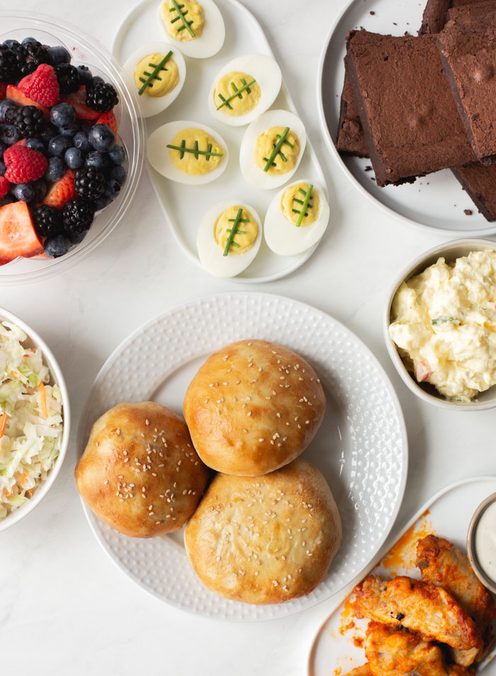 party food spread with stuffed buns, potato salad, deviled eggs, berries, wings and brownies