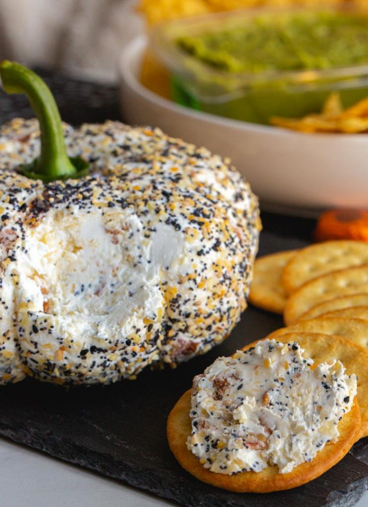 pumpkin shaped everything cheese ball on a platter with a piece taken out and spread on a cracker