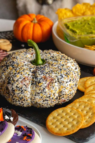 a pumpkin shaped cheese ball covered in everything bagel seasoning and served with crackers