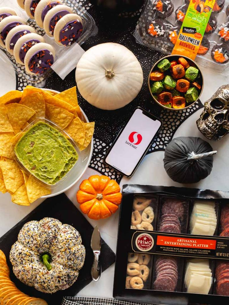 pumpkin everything cheese ball on a platter with an antipasto tray, guacamole and chips, halloween candy, halloween cookies and brownies