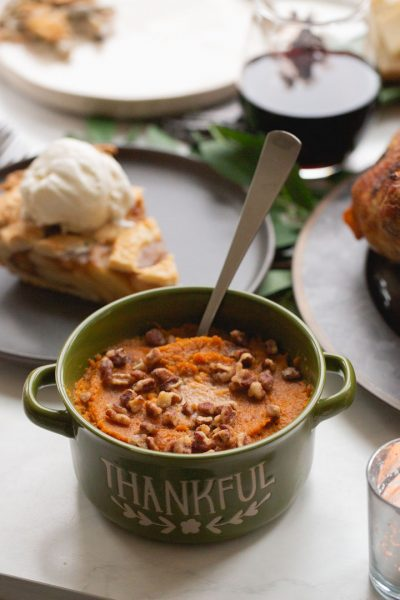 bourbon sweet potatoes in a serving dish with candied pecans on top