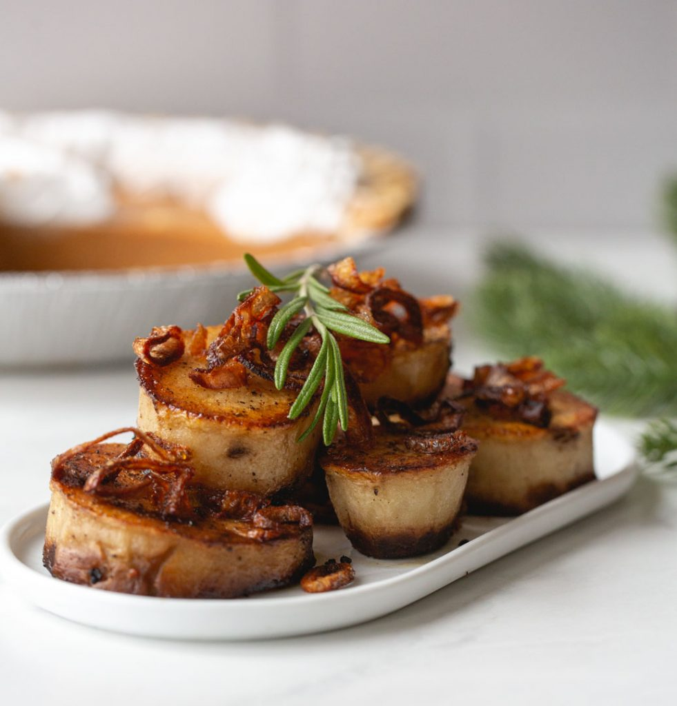 fondant potatoes garnished with fried shallots and rosemary