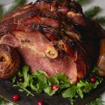 a glazed holiday ham served with baked apples, arugula and cranberries